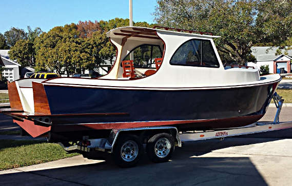 A newly completed 26' picnic boat-style outboard cruiser, loaded on the boat-trailer and ready to launch